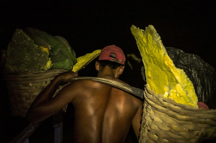 A miner balancing baskets of sulphur on his shoulders.