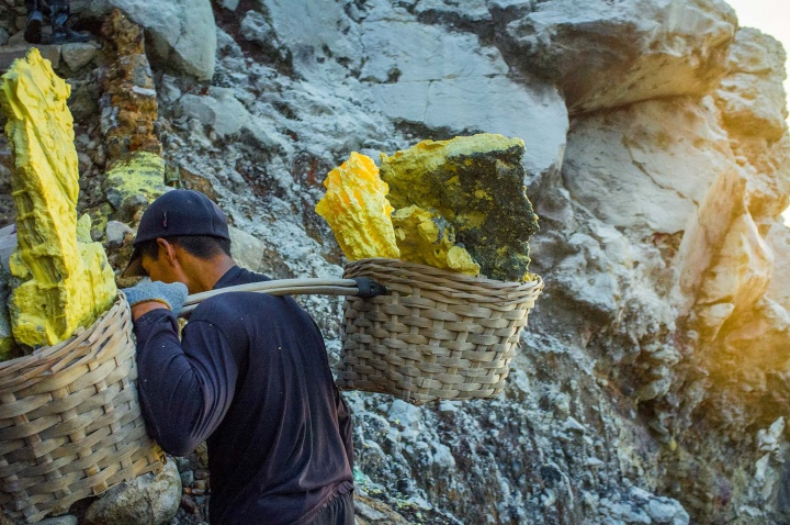 Miner ascends the crater carrying baskets filled with slabs of sulphur. The baskets weigh upto 90kg and miners must carry these one kilometre up the rocky terrain of the caldera and another three kilometres down to the weighing base at the foot of the volcano.