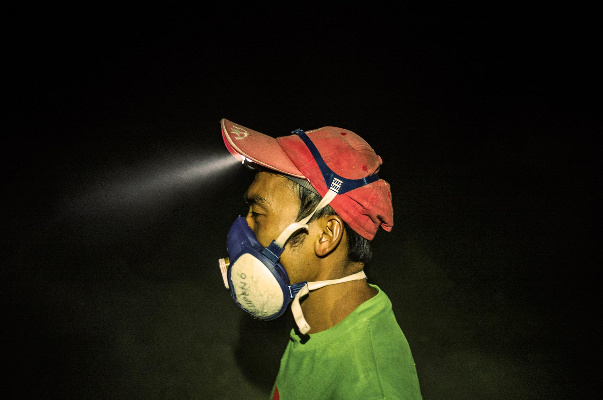 Miner with head torch and respirator.