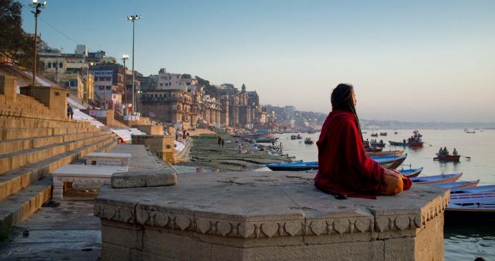 Иностранец медитирует рано утром в древнем городе Индии Варанаси.