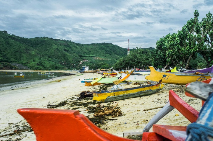 Colourful wooden boats scattered across Kuta beach.