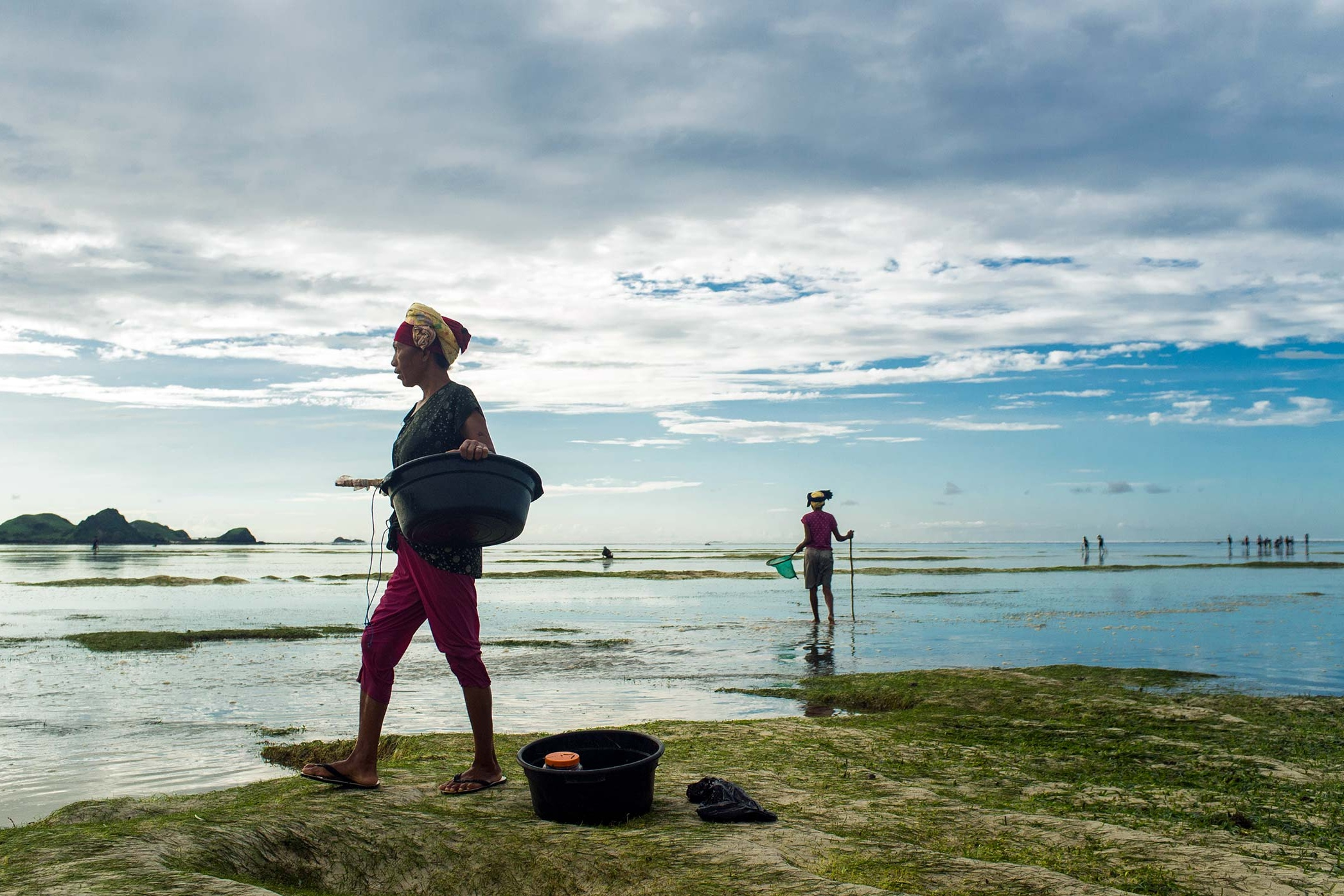 Woman with catch in her basin heads back to the beach.