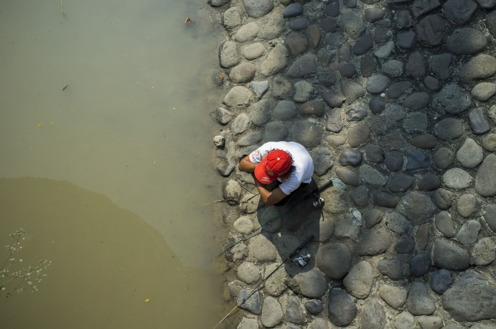 Man fishes in the polluted river.