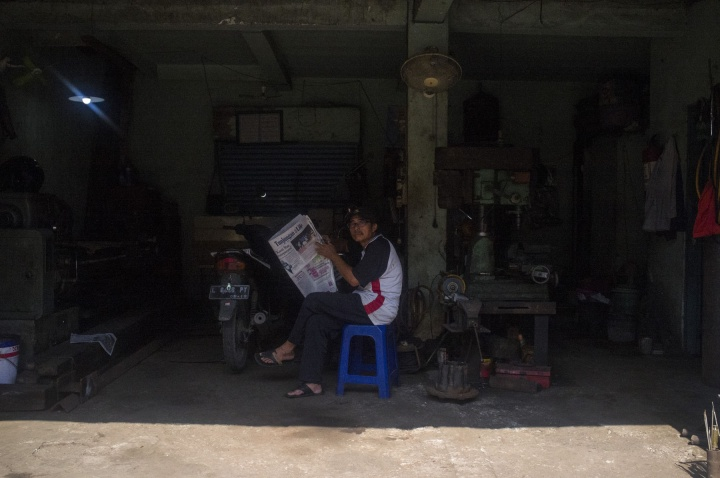 A mechanic reads the paper.
