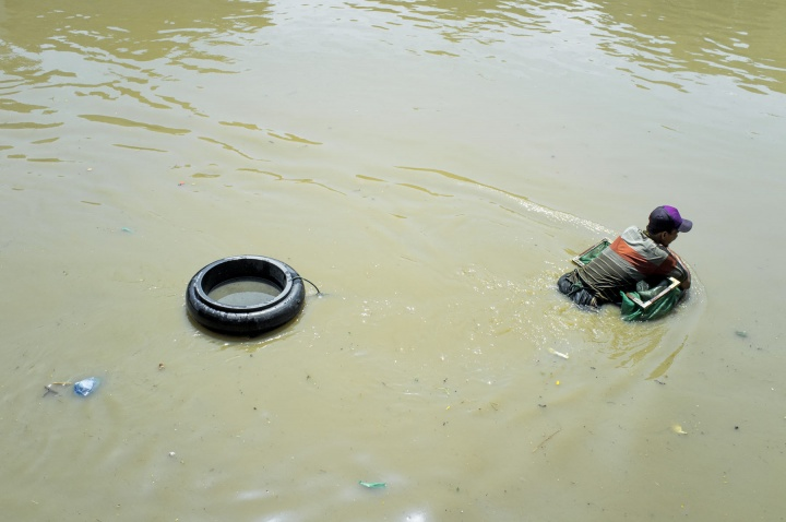A man fishes in the polluted river.