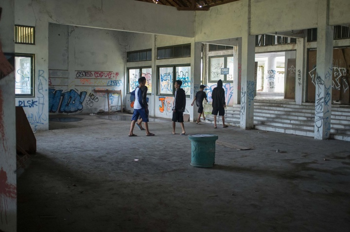 Locals exploring an abandoned hotel in Magelang.