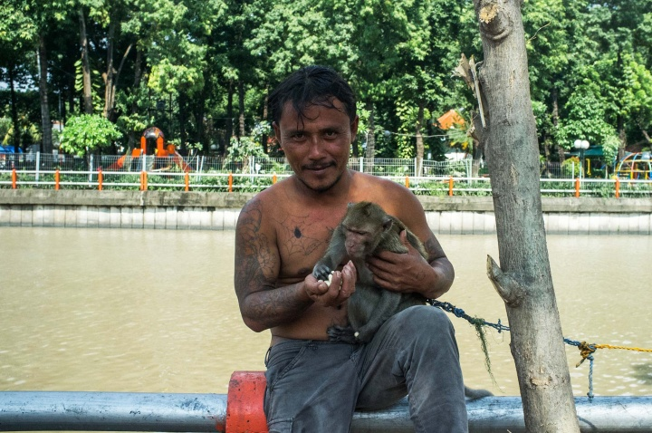 Tattooed man, who looks like a gang member, feeds a monkey tied to a tree on the riverbank.