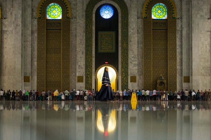 A woman walks to women's area of the mosque for the start of prayers.