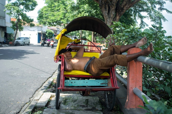 Sleeping becak driver. These becak bikes often serve as a house for their drivers too.