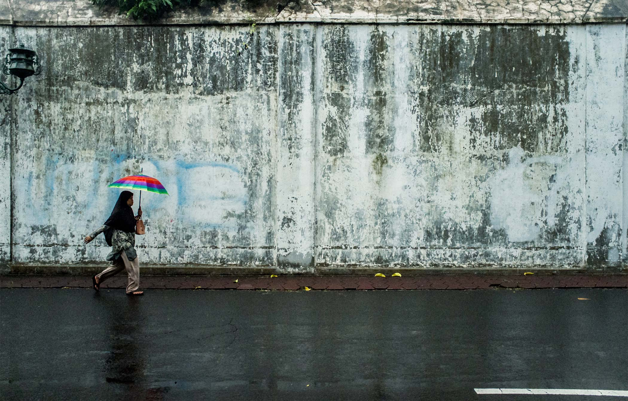A woman with a brightly coloured umbrella walking outside the palace walls.