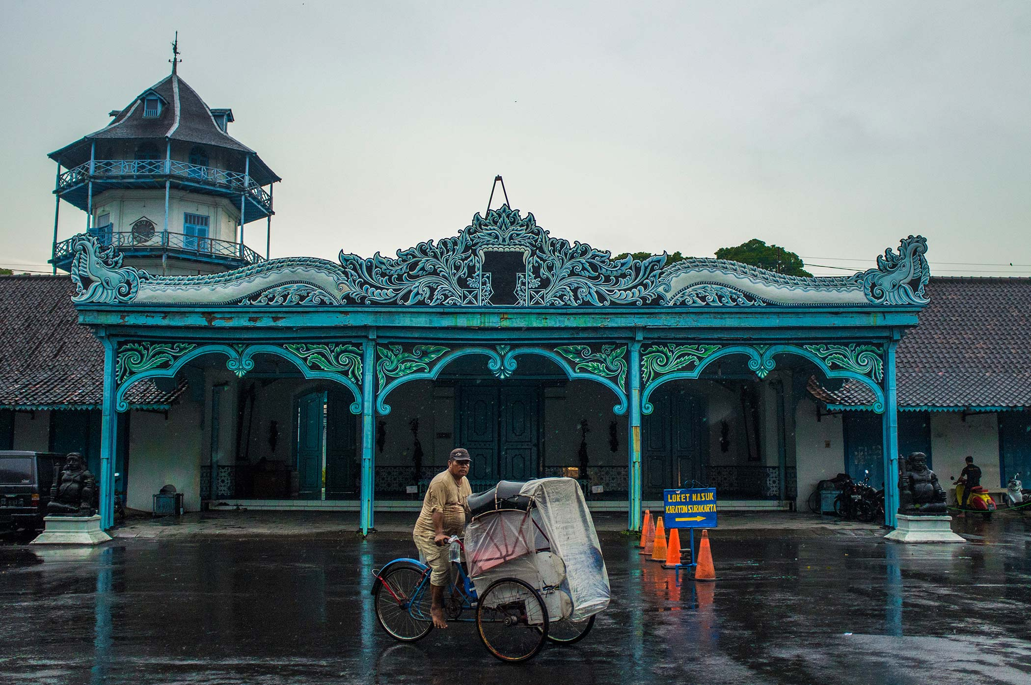 A man on a becak passes the main facade of Baleroto in Kemandungan Lor, the entrance of the Sri Manganti compound in Kraton Surakarta. The clock tower in the background is called Panggung Songgobuwono. The principal residence of the Sultan was the Kraton (palace), sometimes called the Kraton Solo.