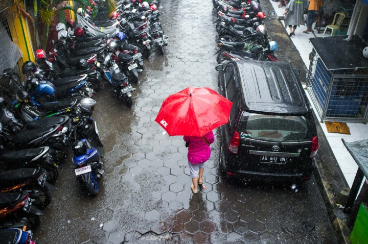 Woman walking under the market bridge and carrying a red umbrella.