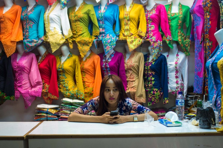 A bored sales lady plays with her phone at Beringharjo market in Jogja.
