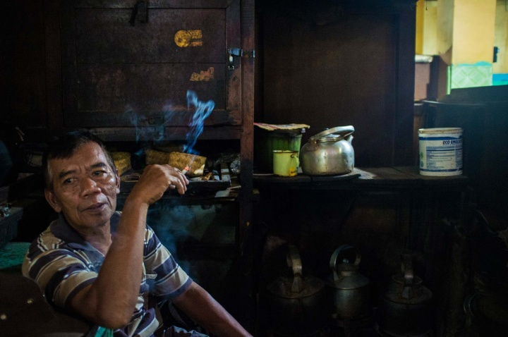 A man smokes in a privately owned warung. God knows what he sells.