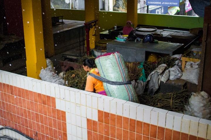 A woman carries spices across Beringharjo market.