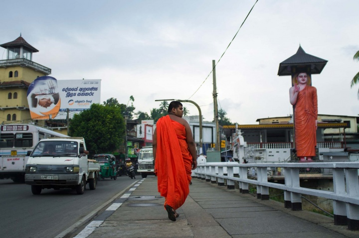 Monk in orange robe is walking down the street in outskirts of Kandy.