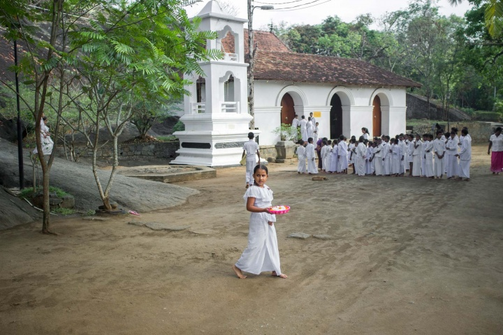 Girl is carrying flowers for the Sunday morning choir before she joins white-dressed crowd of fellow students outside the Buddhist temple.