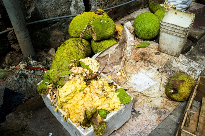 Boxes of squashed durians are piled in boxes outside the old town market in Kandy.